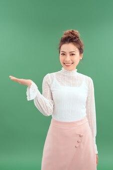 Ritratto di giovane donna asiatica che mostra la sua mano per mostrare il prodotto. isolato su sfondo verde.