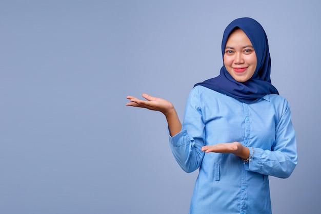 Ritratto di giovane donna asiatica che sorride e che mostra il prodotto