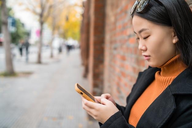 Ritratto di giovane donna asiatica utilizzando il suo telefono cellulare all'aperto in strada. concetto urbano e di comunicazione.