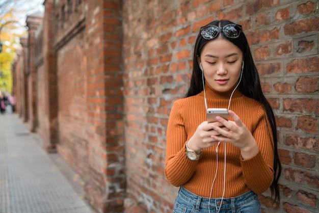 Ritratto di giovane donna asiatica utilizzando il suo telefono cellulare con auricolari all'aperto in strada. concetto urbano e di comunicazione.