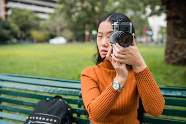Ritratto di giovane donna asiatica utilizzando una fotocamera digitale professionale nel parco all'aperto. concetto di fotografia.