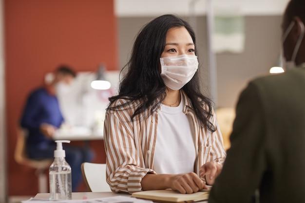 Ritratto di giovane donna asiatica che indossa la maschera durante la riunione di lavoro in ufficio con una bottiglia di disinfettante in primo piano, copia dello spazio