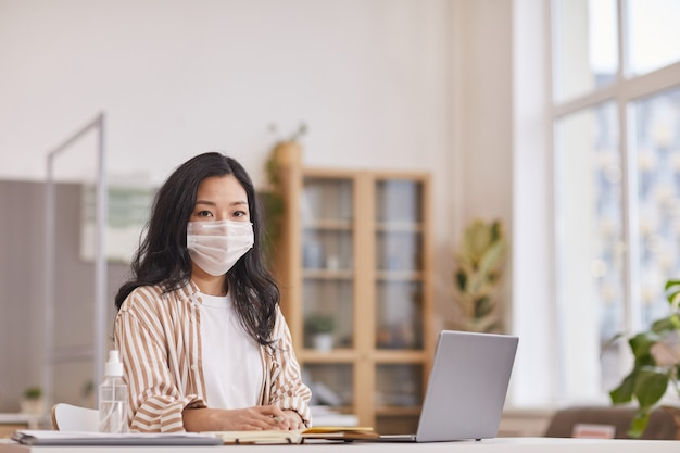 Ritratto di giovane donna asiatica che indossa la maschera e guardando la fotocamera mentre è seduto alla scrivania in ufficio con una bottiglia di disinfettante in primo piano, spazio di copia