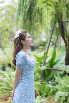 Ritratto di una giovane donna asiatica con un vestito blu che sorride felicemente sullo sfondo del giardino verde.