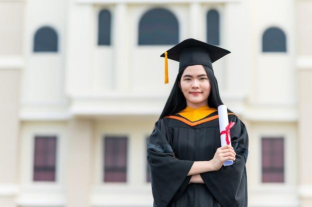Ritratto di giovane donna asiatica con diploma di laurea all'aperto