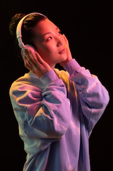 Giovane donna asiatica del ritratto con le cuffie