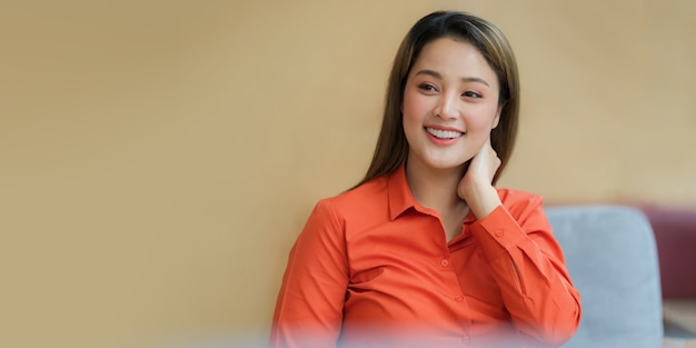 Ritratto di giovane donna asiatica con volto sorridente seduto in ufficio creativo o caffè