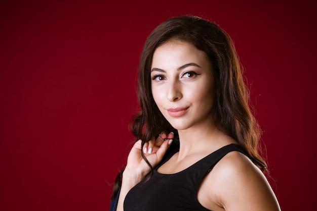 Ritratto di una giovane donna bruna adulta attraente con i capelli lunghi in un top corto nero su uno sfondo scuro...