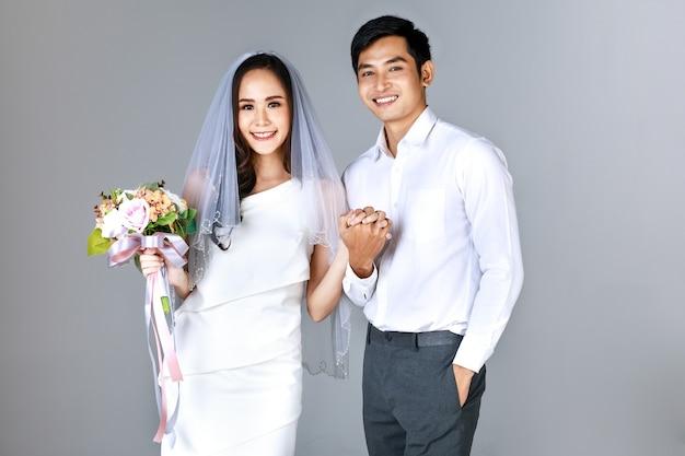 Ritratto di giovane coppia asiatica attraente che si tiene per mano, uomo che indossa una camicia bianca, donna che indossa abito da sposa con velo che tiene un mazzo di fiori. concetto per la fotografia prematrimoniale.