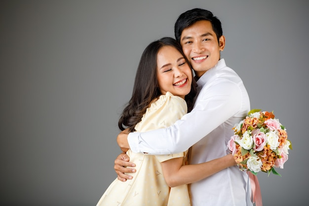 Ritratto di giovane coppia asiatica attraente, uomo che indossa una camicia bianca, donna che indossa un abito beige che si abbraccia, donna che tiene un mazzo di fiori. concetto per la fotografia prematrimoniale.