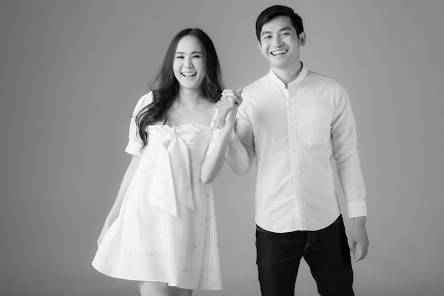 Ritratto di giovane coppia asiatica attraente, uomo che indossa una camicia bianca, donna che indossa un abito bianco in piedi insieme tenendosi per mano nella fotografia in bianco e nero. concetto per la fotografia prematrimoniale.