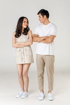 Ritratto di giovane coppia asiatica attraente, uomo che indossa maglietta bianca e pantaloni beige, donna che indossa abito beige in piedi insieme con le braccia incrociate su sfondo bianco. concetto per la fotografia prematrimoniale.