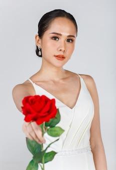 Ritratto di giovane donna asiatica attraente che indossa abito da sposa bianco che tiene una rosa rossa su sfondo bianco. concetto per la fotografia prematrimoniale.