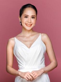 Ritratto di giovane donna asiatica attraente che indossa abito da sposa bianco sorridente su sfondo rosa. concetto per la fotografia prematrimoniale.