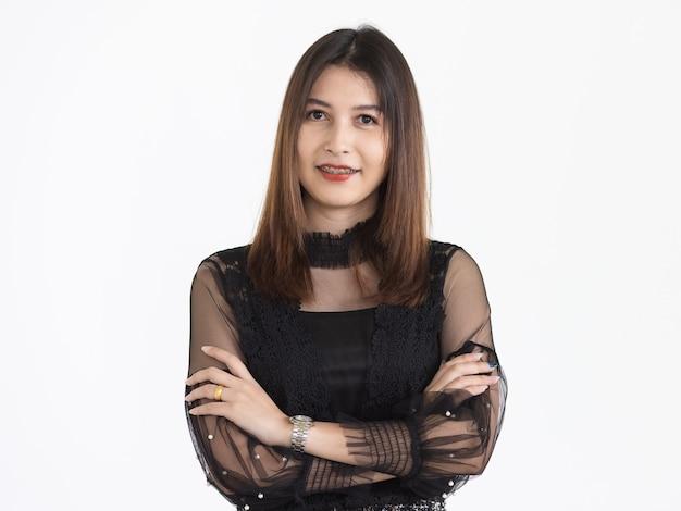 Ritratto di giovane donna asiatica attraente con capelli castani che indossa vestito rivelatore nero che sorride con sicuro. isolato.