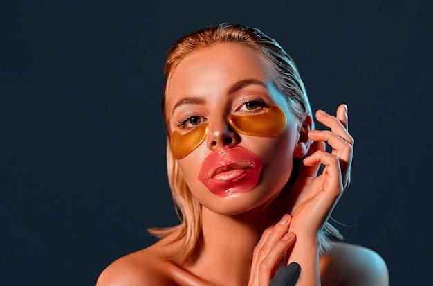 Ritratto di una giovane donna bionda attraente con pelle splendente con macchie sulle labbra e sotto gli occhi su un muro nero