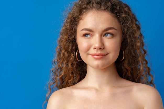 Ritratto di una giovane donna attraente dai capelli ricci su sfondo blu
