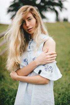 Ritratto di giovane ragazza bionda elegante attraente in vestito romantico blu che posa sopra il fondo della campagna