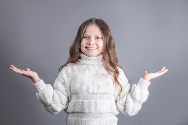 Ritratto di una giovane bambina attraente con capelli biondi in maglione da parte ee si diffonde le mani