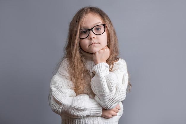 Ritratto di una giovane bambina attraente con i capelli biondi in un maglione bianco che osserva minuziosamente