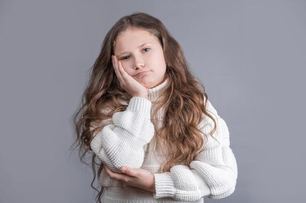 Ritratto di una giovane bambina attraente con capelli biondi lunghi fluenti in un maglione bianco insoddisfatto su uno sfondo grigio studio. copia spazio.