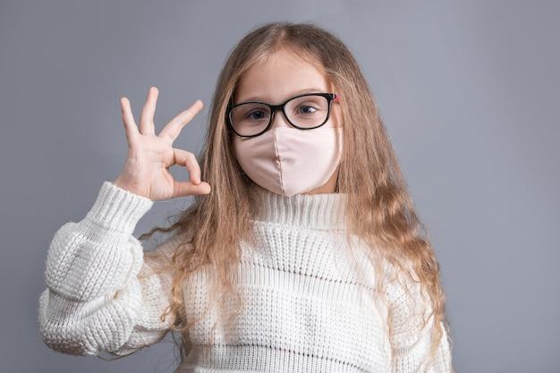 Il ritratto di una giovane bambina attraente con i capelli fluenti lunghi biondi in un maglione bianco nella mascherina protettiva medica mostra il segno giusto