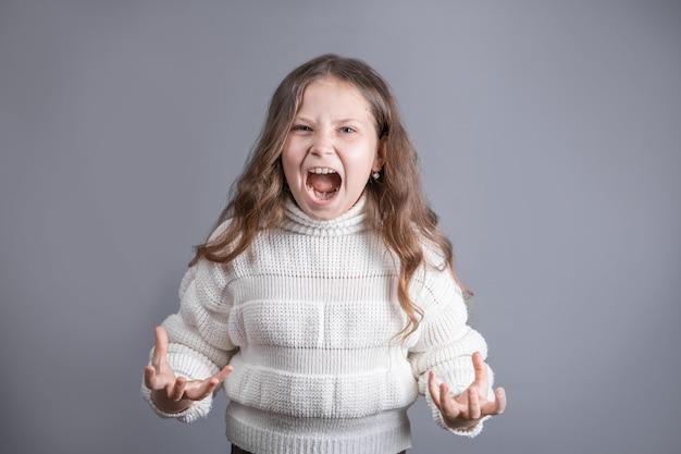 Ritratto di una giovane bambina attraente con lunghi capelli biondi fluenti in un maglione bianco grida gesti con rabbia