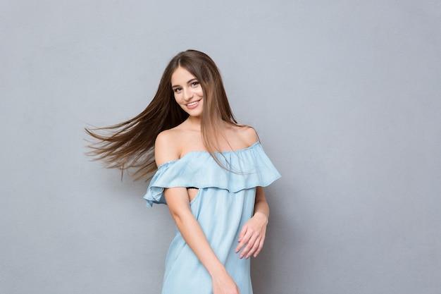 Ritratto di giovane bella ragazza sorridente positiva attraente in vestito blu con capelli volanti