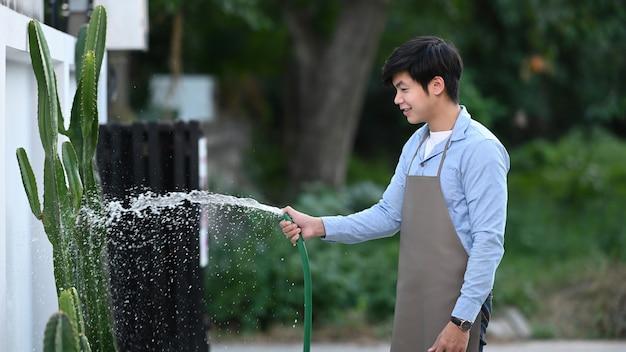 Ritratto di giovane attraente spruzzare acqua dal tubo flessibile che innaffia una pianta a casa.
