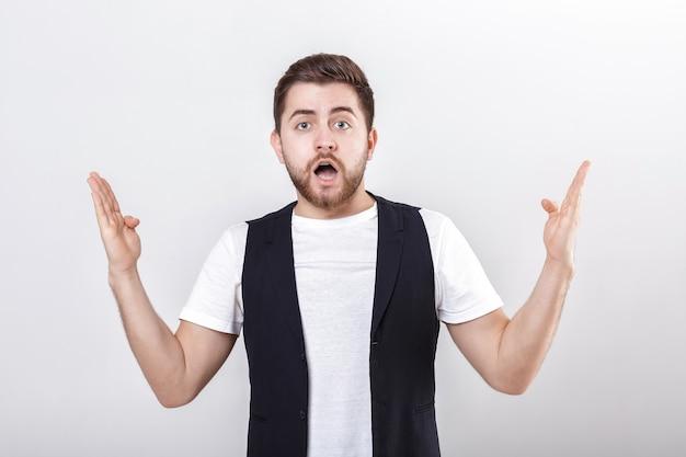 Ritratto di giovane uomo castana sorpreso attraente in camicia bianca su fondo grigio. fatto sorprendente