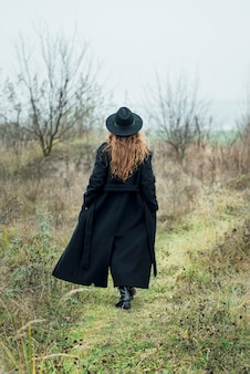 Ritratto di giovane donna attraente in cappotto e cappello neri