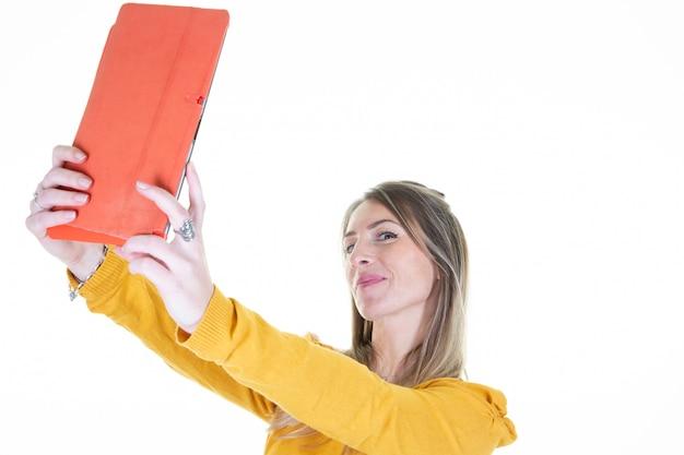 Ritratto di giovane donna attraente che fa la foto del selfie con il computer della compressa sul fondo bianco