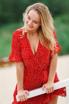 Ritratto di una giovane donna attraente in abito rosso con profonda scollatura all'aperto in una giornata di sole. bella ragazza sorridente con rossetto rosso in breve vestito rosso in estate. ritratto di donna bionda felice all'aperto