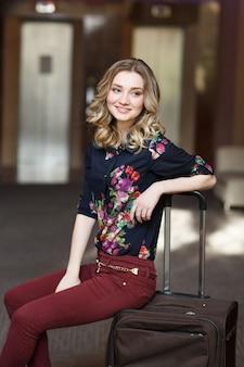Giovane donna attraente del ritratto che si siede sulle valigie nel terminale o nella stazione ferroviaria. la ragazza si è incontrata durante un viaggio.