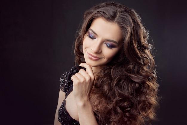 Ritratto di una giovane donna attraente con splendidi capelli ricci. bruna attraente