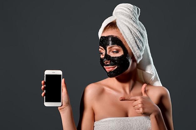 Ritratto di una giovane donna attraente con un asciugamano sulla testa con una maschera detergente nera sul viso con un telefono su una parete grigia.