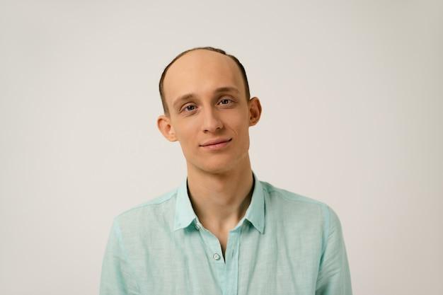 Ritratto di giovane uomo calvo con divertenti orecchie sporgenti in camicia blu corallo con guardando davanti isolato sopra il muro bianco in studio
