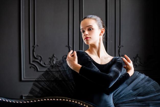 Ritratto di una ragazza giovane ballerina in un tutù nero su uno sfondo scuro