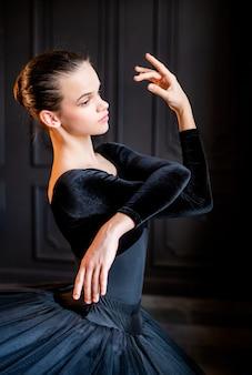 Ritratto di una ragazza giovane ballerina in un tutù nero su una parete scura
