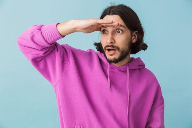 Ritratto di un giovane uomo brunetta barbuto che indossa una felpa con cappuccio in piedi isolato sul muro blu, guardando lontano