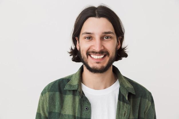 Ritratto di un giovane uomo brunetta barbuto che indossa una camicia a quadri in piedi isolato su un muro bianco, sorridente