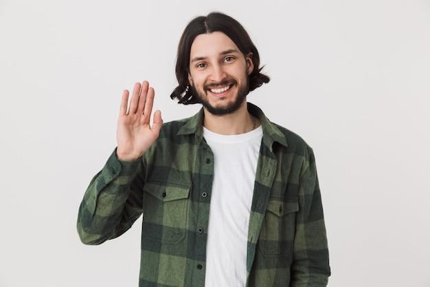 Ritratto di un giovane uomo brunetta barbuto che indossa una camicia a quadri in piedi isolato su un muro bianco, agitando la mano