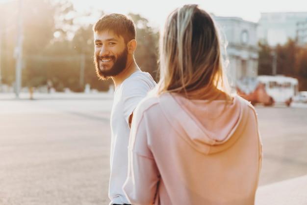 Ritratto di un giovane uomo caucasico barbuto sorridente e guardando la sua ragazza mentre la sta conducendo per strada contro l'alba mentre si incontra al mattino.