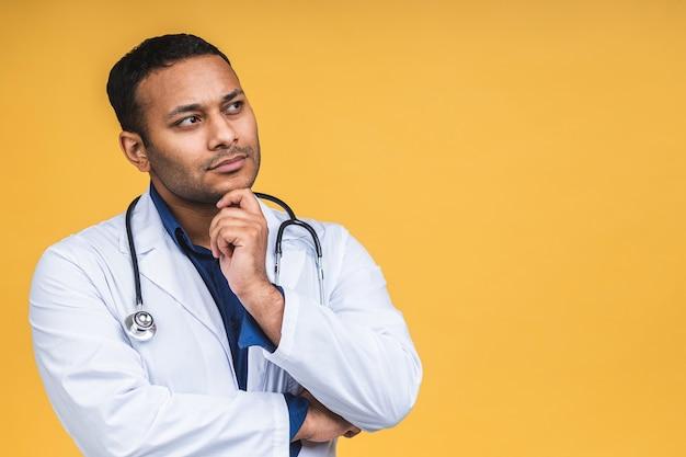 Ritratto giovane medico barbuto con lo stetoscopio sul collo in cappotto medico in piedi contro isolato su sfondo giallo.