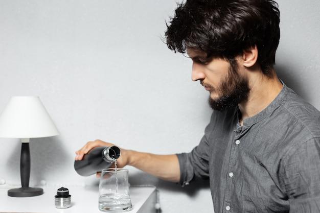 Ritratto di giovane ragazzo barbuto con i capelli arruffati, versa l'acqua nel bicchiere dalla bottiglia termica in acciaio
