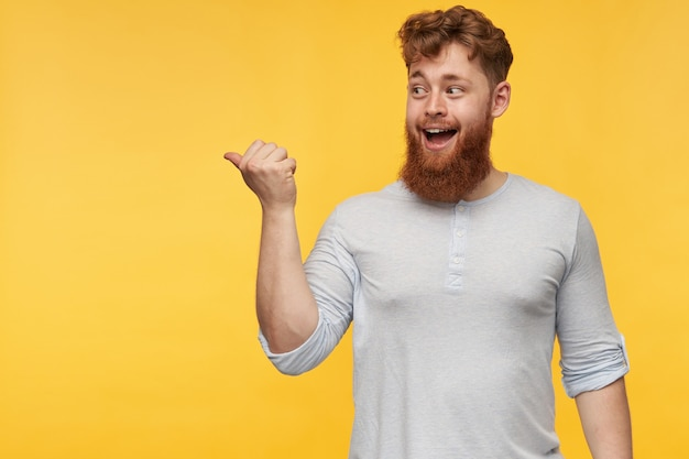 Ritratto di giovane ragazzo barbuto con i capelli rossi, si sente felice e sorridente mentre indica nello spazio della copia sul lato sinistro del giallo.