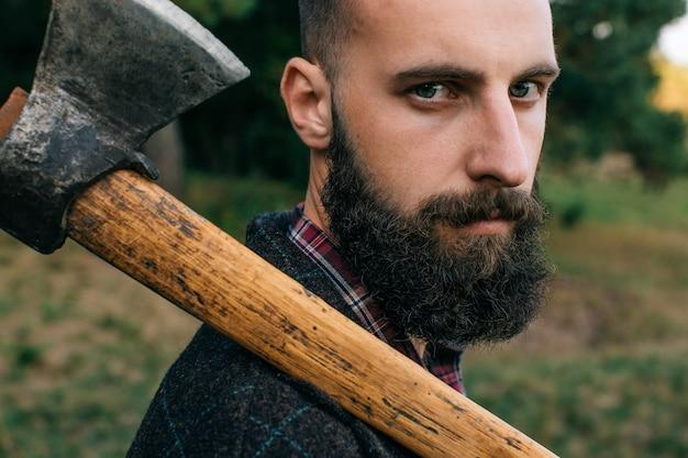 Ritratto di giovane logger barbuto hipster con ascia nella foresta