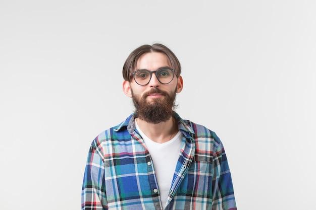 Ritratto di un ragazzo elegante giovane barbuto hipster su sfondo bianco.