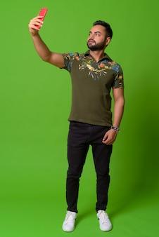 Ritratto di giovane barbuto uomo indiano sul verde