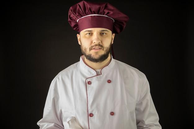 Ritratto di giovane chef maschio barbuto in uniforme